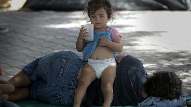 Una niña descansa junto a su madre en un pequeño campamento para migrantes justo a la entrada del Puente Internacional Gateway, en Matamoros, México. (el Nuevo Herald)