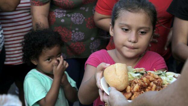Los niños migrantes hacen fila para comer en un campamento ubicado en la entrada del Puente Internacional que conecta a Matamoros con Brownsville, en Texas. (el Nuevo Herald)
