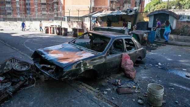 Restos de un vehículo incendiado en una calle donde hubo protestas este martes en Caracas. (EFE/Miguel Gutiérrez)