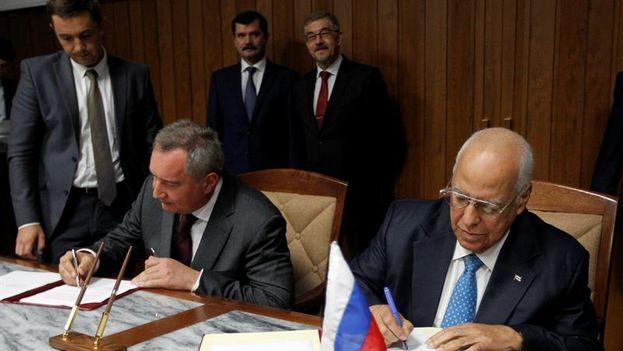 Ricardo Cabrisas Ruiz y el vicepresidente de Rusia, Dmitry O. Rogozyn firman diferentes acuerdos este jueves entre Cuba y Rusia. (EFE/Ernesto Mastrascusa)