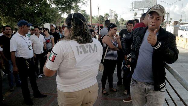 Ronald Sicilia Espinosa (derecha), un emigrante cubano, da el visto bueno a sus simpatizantes después de ser el primer número llamado para cruzar a Estados Unidos a pedir asilo. (el Nuevo Herald)