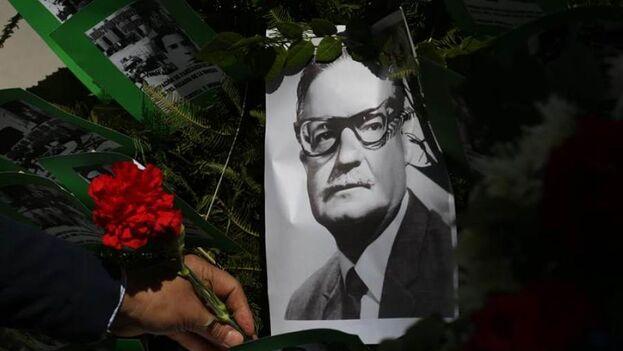 Un hombre deja una flor sobre la imagen del presidente chileno Salvador Allende, este viernes en Santiago. (EFE/Elvis González)