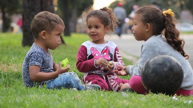 Brian Steven Tole, Edilianys Rojas y Ediangelis Alexandra Rojas juegan a las afueras de una de las terminales de buses en la ciudad de Bogotá mientras sus padres se dedican a vender caramelos y café para poder pagar un lugar donde pasar la noche. (14ymedio)