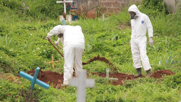 Trabajadores gubernamentales entierran un féretro con una víctima de covid-19 en el cementerio de San Cristóbal, estado de Táchira (Venezuela). (EFE/Johnny Parra/Archivo)