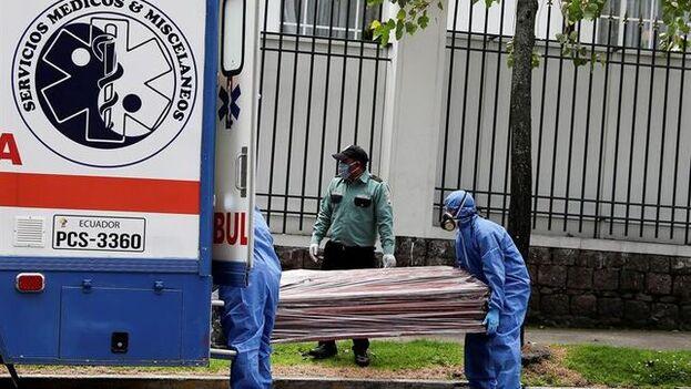 Trabajadores de un servicio médico cargan un féretro a las puertas de una funeraria en Quito. (EFE)