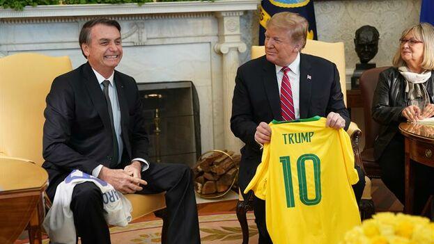 Trump y Bolsonaro, que exhibieron su buena sintonía, se intercambiaron camisetas deportivas con sus nombres. (EFE/ Chris Kleponis)
