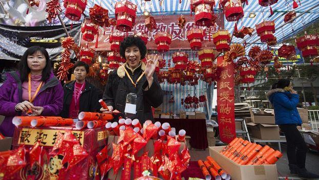 Varias mujeres posan junto a un puesto de adornos de la Feria del Año Nuevo en China. (EFE)