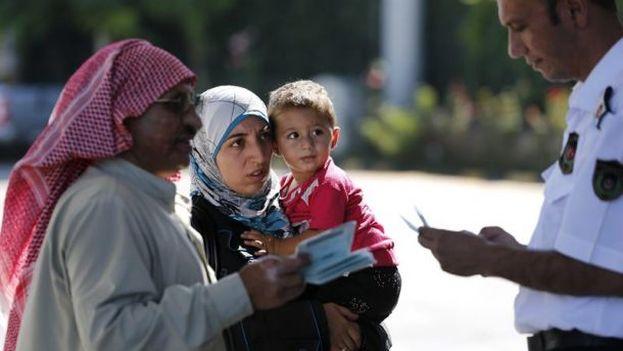 Varios sirios presentan su documentación en la aduana mientras intentan cruzar a Turquía en el puesto de Cilvegozu, fronterizo con Siria. (EFE)