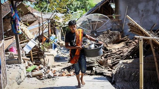 Varios vecinos caminan entre los escombros tras el terremoto de magnitud 6,9 que sacudió la noche del domingo la isla de Lombok, en Indonesia. (EFE)