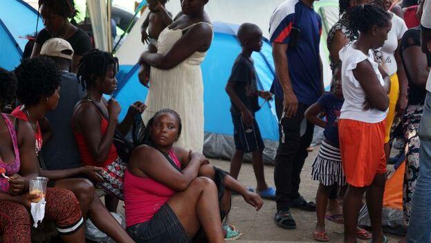 Varios migrantes esperan para recibir atención médica durante su estancia en el albergue de Tapachula. (EFE/Carlos López)