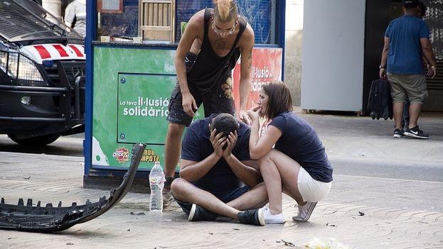 Varios jóvenes permanecen junto a los restos de un vehículo, en el lugar del atentado ocurrido el pasado jueves en las Rambla de Barcelona. (EFE)