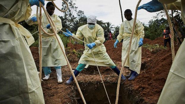 Varios trabajadores de salud entierran a una víctima de ébola, en Beni, Congo. (EFE)