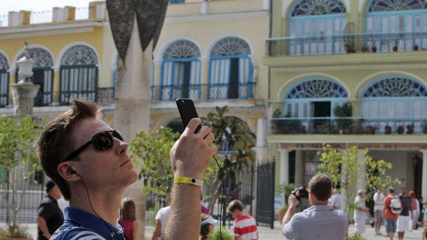 Varios turistas toman fotos en una plaza en La Habana. (EFE)