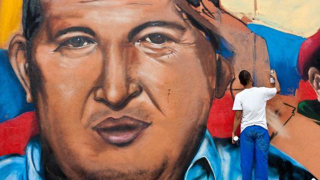 Un grupo de grafiteros pintan un muro con el rostro del presidente de Venezuela, Hugo Chávez. (Miguel Gutiérrez/EFE)