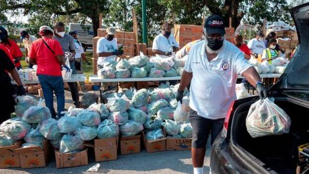 Voluntarios del sur de Florida que entregan bolsas de comida a los residentes de Opa-Locka en el Parque Sherbondy. (EFE)