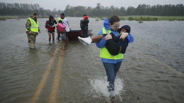 Voluntarios del Equipo Civil de Respuesta a Crisis ayudan a rescatar a tres niños de su hogar inundado el 14 de septiembre de 2018 en James City, Estados Unidos. (el Nuevo Herald)