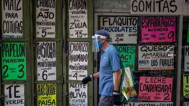 Un hombre camina frente a una vitrina de la que cuelgan carteles con precios de alimentos el 15 de octubre de 2020, en Caracas. (EFE/ Miguel Gutiérrez)