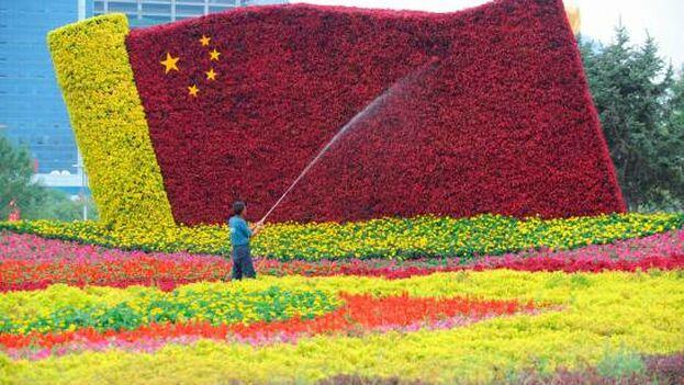 Un hombre riega un jardín de flores para conmemorar el 70 aniversario de la República Popular China. (EFE)