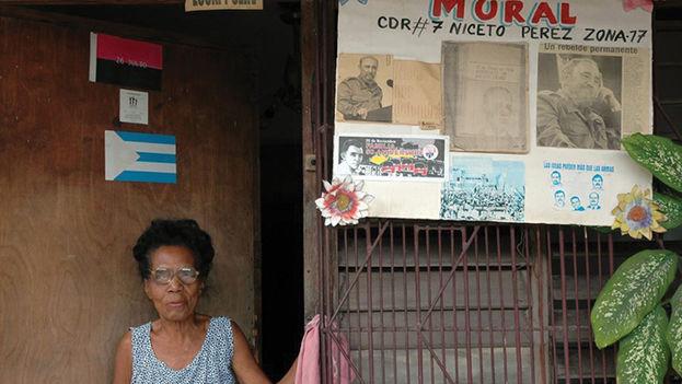 Una mujer en la entrada de su casa con un mural que anuncia el Comité de Defensa de la Revolución de su barrio. (EFE)