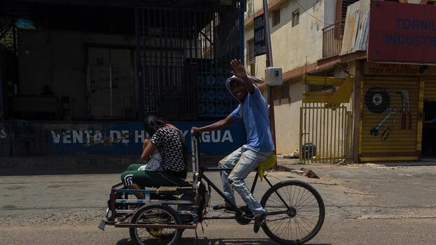 Un hombre conduce una bicicleta modificada mientras transporta a un pasajero en Maracaibo. (EFE)