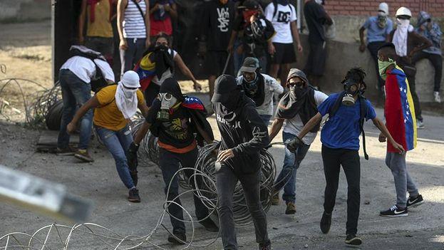 Un grupo de personas bloquean una calle durante las protestas que convulsionan a Venezuela. (EFE)