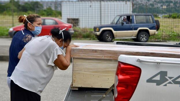 Un familiar de un fallecido llora a las afueras del cementerio Jardines de la Esperanza este domingo en Guayaquil. (EFE)