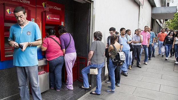 """Los clientes hacen largas colas en los cajeros automáticos esperando que la pantalla no anuncie """"fuera de servicio"""" si quien estaba delante sacó los últimos 3.000 bolívares. (EFE)"""