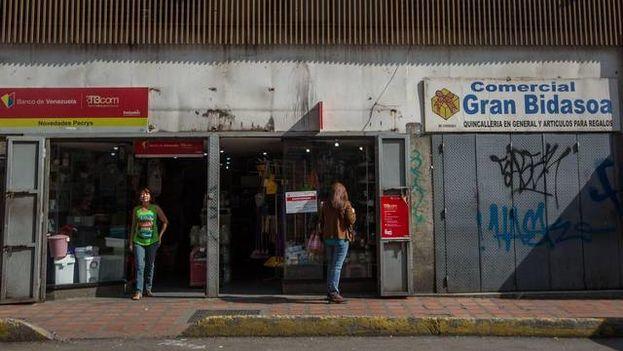 Un local comercial abierto y otro cerrado durante la huelga de este 28 de octubre de 2016. (EFE)
