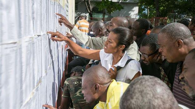 Los votantes consultan en el censo buscan sus mesas de elección en Puerto Príncipe. (EFE/Orlando Barría)