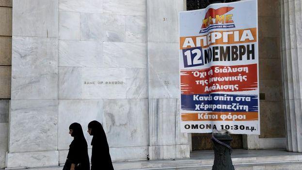 Dos monjas caminan junto al cartel de la huelga convocada por los dos principales sindicatos del país en contra de las medidas de recorte del tercer rescate. (EFE/Yannis Kolesidis)