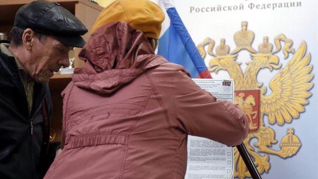 Una mujer introduce la papeleta en la urna durante las elecciones legislativas de Rusia. (EFE/EPA/Maxim Shipenkov)