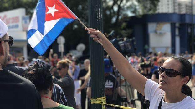 Una mujer enarbola una bandera cubana para celebrar el fin de Fidel Castro. (14ymedio)