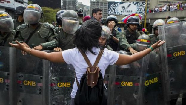 Una joven se enfrenta a la Policía durante una protesta en Venezuela. (EFE)
