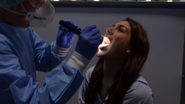 Un especialista del aeropuerto de Viena recoge una muestra de saliva de una pasajera para realizarle un test rápido de antígenos, antes de que la pasajera pueda acceder a la puerta de embarque. (EFE/Jorge Dastis)