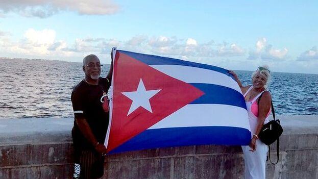 Una pareja de cubanos extiende una bandera nacional frente a la bahía en Miami, Florida. (EFE/Ana Mengotti)
