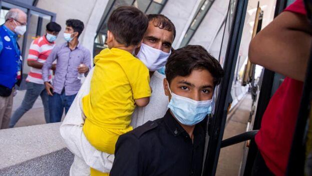 Los refugiados andan rápido por el aeropuerto mientras un funcionario del Departamento de Estado de EE UU les hace señas. (EFE)
