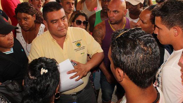 Un funcionario de Migración atiende a un centenar de migrantes cubanos que reclaman no haber sido incluidos en la lista. (EFE/ Marcelino Rosario)