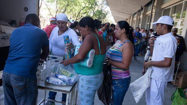 """Una mujer compra alimentos en una venta realizada en un edificio del plan habitacional gubernamental """"Misión Vivienda"""". (Miguel Gutiérrez/EFE)"""