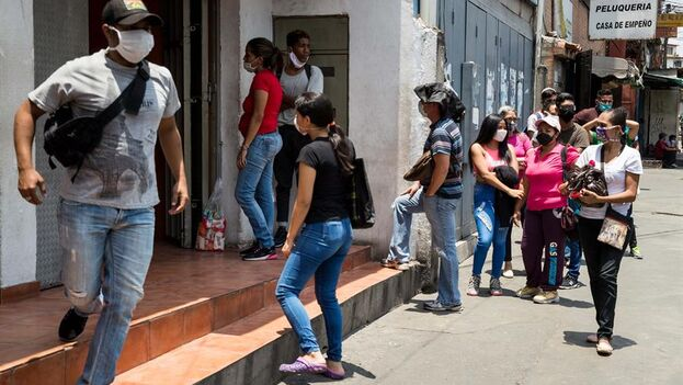 Un grupo de personas haciendo fila para entrar a una tienda, en Las Minas de Baruta, en Caracas. (EFE)