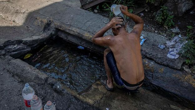 Un hombre se baña con agua de una alcantarilla en Caracas. (EFE/Rayner Peña)