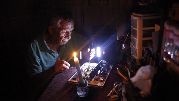 Un hombre repara un electrodoméstico durante un corte de luz este lunes. (EFE/STR)
