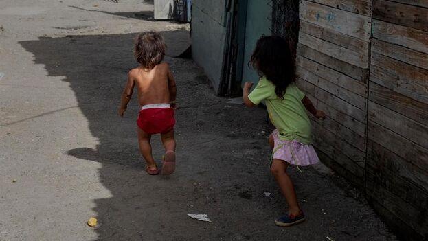 Dos niños juegan entre las viviendas improvisadas en un terreno ocupado en Caracas. (EFE/ Rayner Peña R)