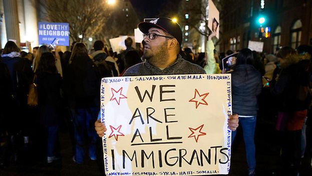 """Un hombre sostiene una pancarta en la que se lee """"todos somos inmigrantes"""" en una protesta contra la decisión del presidente Donald Trump de vetar la entrada de refugiados musulmanes. (EFE)"""
