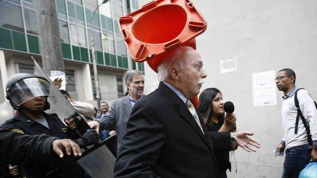 Un diputado peruano es golpeado por un cono de tráfico mientras intentaba ingresar a un edificio. (El Comercio de Perú)