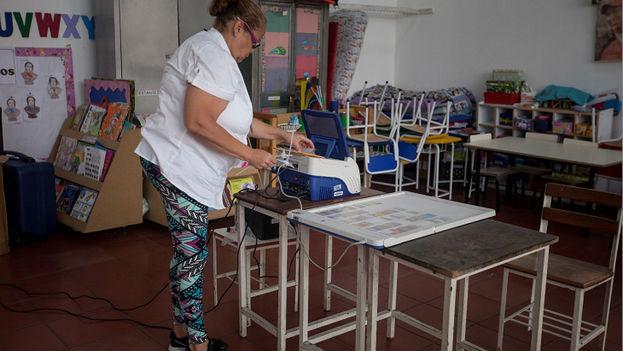 Un miembro de la mesa electoral prepara una máquina de votación antes de las elecciones legislativas en Caracas (Foto EFE/Miguel Gutiérrez)
