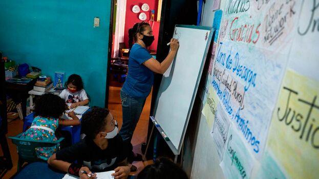 Las maestras apoyan a los alumnos a resolver las tareas que los colegios envían vía correo electrónico o WhatsApp. (EFE)