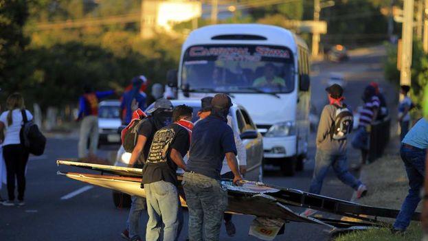 Un grupo de manifestantes destruye una valla en Tegucigalpa, Honduras, en medio de las protestas desatadas desde el miércoles en las calles. (EFE)