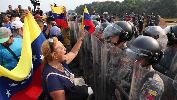 Un grupo de manifestantes se enfrentan a los soldados chavistas que impiden el paso de la ayuda humanitaria. (EFE)