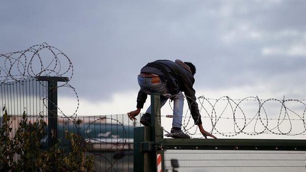 Un migrante salta una cerca antes de intentar tomar un tren en su ruta hacia Inglaterra, en Calais. (EFE/YOAN VALAT)