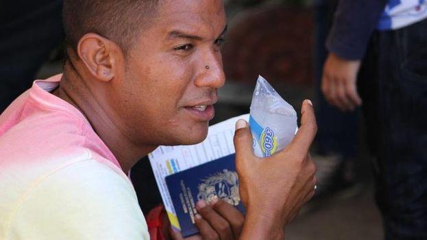 Un migrante venezolano se hidrata tras pasar horas haciendo fila para entrar legalmente a Colombia en Cúcuta. (14ymedio)